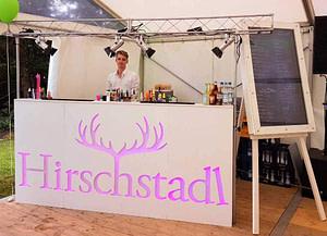 weiße mobile Bar mit Barkeeper. Die Front der Bar ist mit einem pinken Hirschstadlogo versehen.