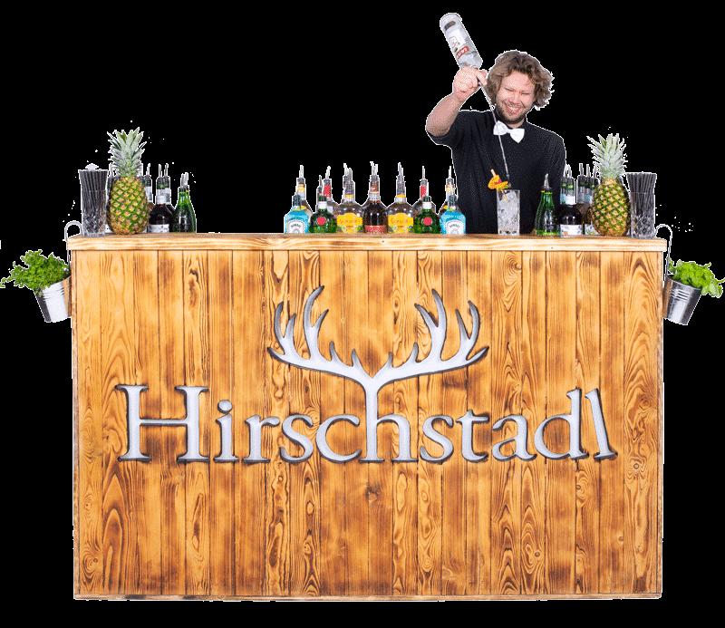 Hirschstadl mobile Cocktailbar mit einer geflammten Holzoptik. auf der mobile Cocktailbar stehen Flaschen und zwei Ananas. Hinter der Bar steht Korbi Krinner als Barkeeper.